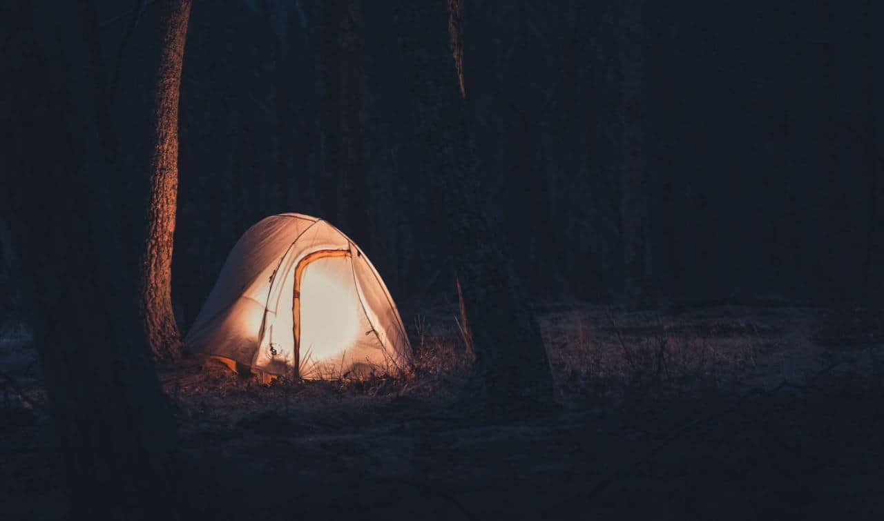 A lit camping tent in the forest