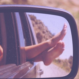 Feet hanging out of the car on a long road trip