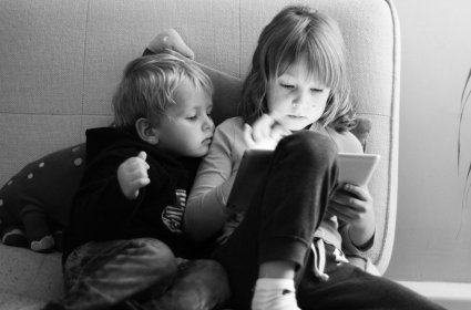 Two kids watching an electronic screen