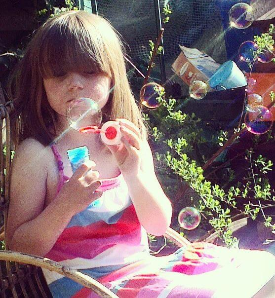 Exhausted girl blowing bubbles after school is over