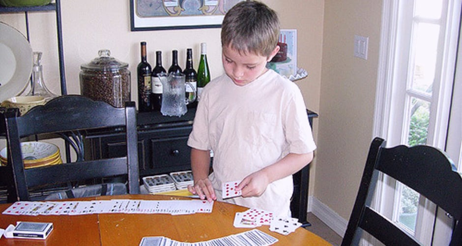 A child learning a magic trick with a deck of cards