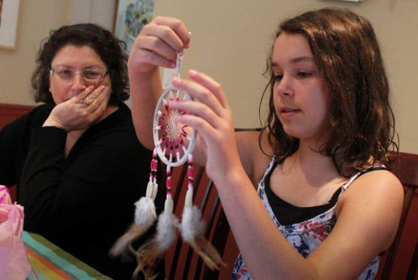 A 5th grader making a homemade Indian dream catcher
