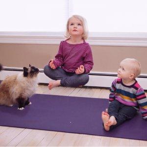 Two blonde homeschool girls doing yoga on a mat
