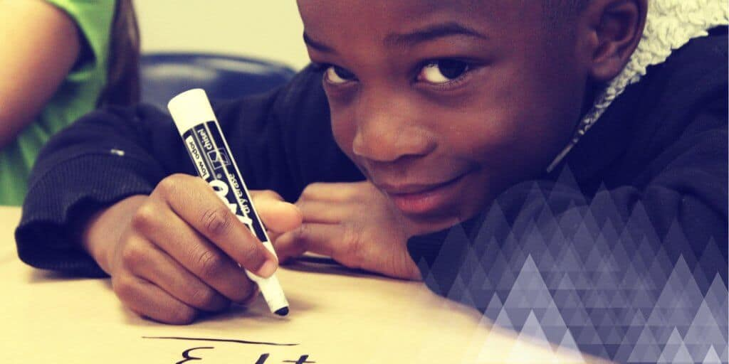 A young boy doing a math game with a dry erase marker