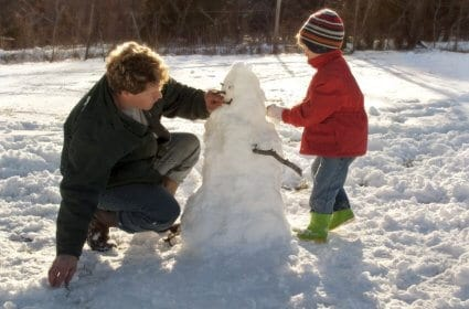 Father and son building a snowman outside