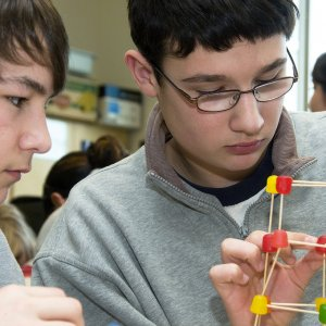 Middle school students piece together a bridge they've designed using toothpicks and gumdrops.