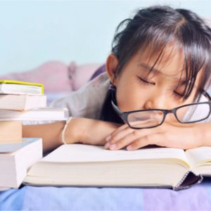 A girl falling asleep with glasses falling off her head
