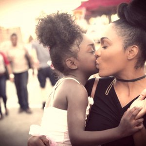 A mother kissing her daughter's cheek