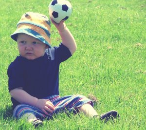 Boy holding a soccer ball in a field
