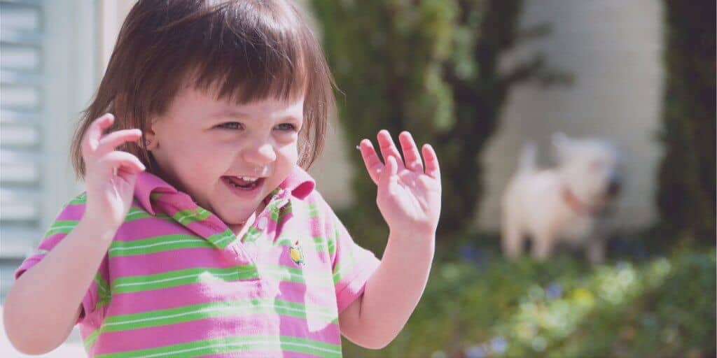 Excited child throwing up hands